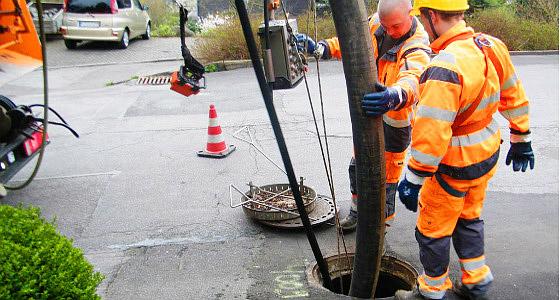 Двама експерти от екипа на Никман Канал сервиз решават проблем със запушване на канализация чрез хидродинамичен метод